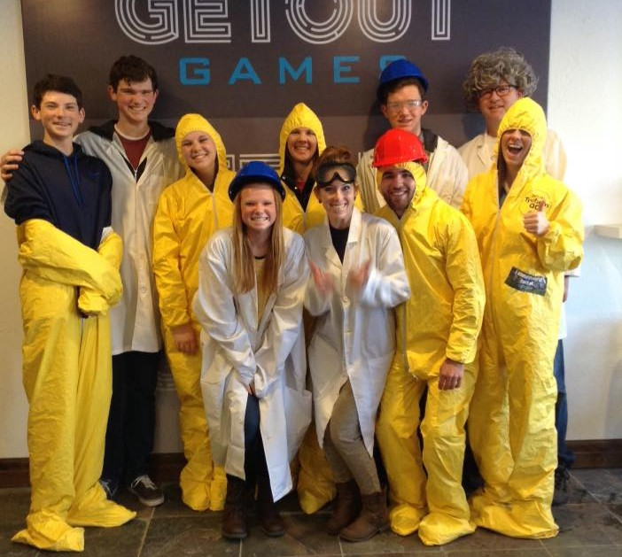 a group of friends pose in costumer after completing an escape room at Getout Games